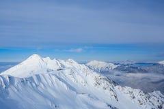 Het voortbouwen op de bovenkant van bergen met sneeuw in de skitoevlucht die van Sotchi Rosa Khutor worden behandeld Royalty-vrije Stock Afbeeldingen