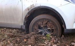 Het voorwiel van auto werd geworden geplakt in de modder Stock Foto's