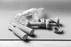 Het vormen en geschiktheidsmateriaal Sporten en gezond levensstijlconcept Barbells en touwtjespringen Stock Afbeelding