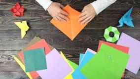 Het vouwen van origamidocument in driehoek, hoogste mening stock video