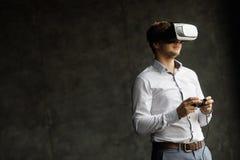 Het VR-hoofdtelefoonontwerp is generisch en geen emblemen, Mens die virtuele werkelijkheidsbeschermende brillen dragen die op fil Stock Fotografie