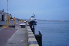 Het vrachtschip verbond voor het dok bij de zeehaven, schuine stand, brede hoekmening, zonnige dag, blauwe hemel Vanglijnen, schi royalty-vrije stock foto