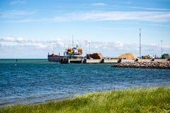 Het vrachtschip verlaat haven weg varend Stock Afbeeldingen