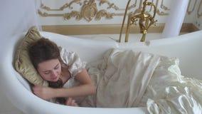 Het vreemde meisje in baltoga zet hoofdkussen onder haar hoofd dicht omhoog liggend in het bad en de slaap stock footage