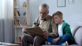 Het vriendelijke oude sprookje van de mensenlezing aan kleinzoon, volgzame jongen die tegen schouder leunen stock fotografie