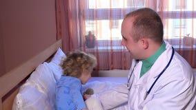 Het vriendschappelijke artsenspel en omhelst met drie éénjarigen zieke patiënt tijdens bezoek stock footage