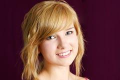 Het vriendschappelijke blonde tienermeisje glimlachen Stock Afbeeldingen