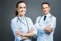 Het vriendschappelijke kijken het vrouwelijke arts stellen met gekruiste handen royalty-vrije stock afbeeldingen