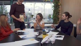 Het vriendschappelijke team is zeer gelukkig om het probleem op te lossen en het grappige vrolijke lid werpt popcorn bij de colle stock videobeelden