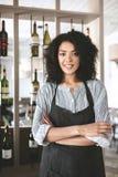 Het vrij Afrikaanse Amerikaanse meisje in schort die bevinden zich met clasped indient restaurant Jong meisje met donker krullend royalty-vrije stock afbeeldingen