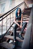 Het vrij blauw-haired informele model van het rotsmeisje, gekleed in zwarte leerbroek en onderwerp, zit op trap Stock Afbeelding