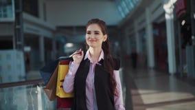 Het vrij gelukkige meisje met mooie samenstelling in het roze overhemd en het zwarte sleeveless jasje loopt in het winkelcentrum stock video