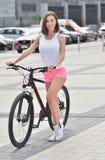 Het vrij geschikte meisje berijdt op fiets in de stad stock afbeeldingen