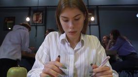 Het vrij jonge meisje in de bibliotheek of in koffie drukt iets op de computer op de achtergrond van communicerende jongelui stock video