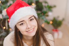 Het vrij jonge meisje in de hoed van de Kerstman zit en glimlacht dichtbij de Kerstmisboom, in rode sokken De achtergrond van Bok Royalty-vrije Stock Foto's