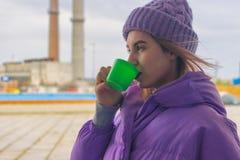 Het vrij jonge meisje drinkt koffie of thee, straat stock afbeelding