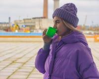 Het vrij jonge meisje drinkt koffie of thee, straat royalty-vrije stock foto