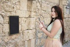 Het vrij jonge meisje houdt telefoon in haar handen en glimlach Stock Foto's
