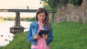 Het vrij jonge meisje loopt langs de waterkant en het gebruiken van tabletcomputer met oortelefoons Brug en uitstekende muur van  stock videobeelden