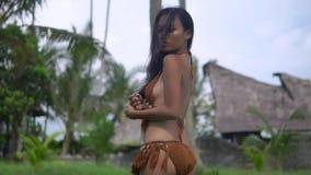 Het vrij jonge oosterse model in bikini met ontzagwekkend cijfer gaat door exotisch dorp stock videobeelden