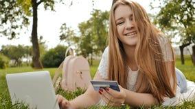 Het vrij jonge studentenmeisje maakt aankopen online gebruikend een creditcard en laptop computer stock afbeeldingen
