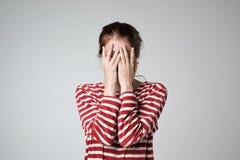 Het vrij Kaukasische meisje behandelt haar gezicht met haar handen stock afbeeldingen