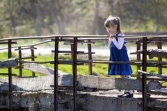 Het vrij kleine blonde langharige meisje in aardige blauwe kleding bevindt zich al Stock Afbeelding