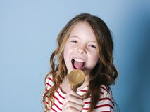Het vrij koele en jonge meisje gebruikt kokende lepel als microfoon en zingt voor blauwe achtergrond en heeft heel wat pret royalty-vrije stock afbeeldingen