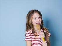 Het vrij koele en jonge meisje gebruikt kokende lepel als microfoon en zingt voor blauwe achtergrond en heeft heel wat pret royalty-vrije stock foto's