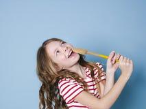 Het vrij koele en jonge meisje gebruikt kokende lepel als microfoon en zingt voor blauwe achtergrond en heeft heel wat pret stock afbeeldingen