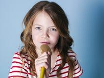 Het vrij koele en jonge meisje gebruikt kokende lepel als microfoon en zingt voor blauwe achtergrond en heeft heel wat pret stock afbeelding