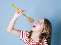 Het vrij koele en jonge meisje gebruikt kokende lepel als microfoon en zingt voor blauwe achtergrond en heeft heel wat pret stock foto