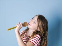 Het vrij koele en jonge meisje gebruikt kokende lepel als microfoon en zingt voor blauwe achtergrond en heeft heel wat pret stock fotografie