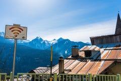 Het vrije WiFi-streekteken, tin, roestte dak en snow-capped bergen op de achtergrond stock fotografie