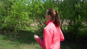 Het vroege Ochtend Mooie Meisje in Roze Sweater stoot in het Hout in de Vroege Lente, op een Achtergrond van Bomen met Jongelui a stock footage