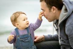 Het vrolijke éénjarige kind raakt zijn father& x27; s neus Royalty-vrije Stock Foto's