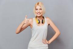Het vrolijke aantrekkelijke jonge vrouw tonen beduimelt omhoog Stock Foto