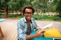 Het vrolijke Afrikaanse boek van de jonge mensenlezing in openlucht Royalty-vrije Stock Afbeeldingen