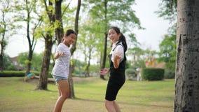 Het vrolijke Aziatische tiener spelen in openbaar park stock video