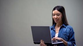 Het vrolijke Aziatische vrouw typen op laptop die zich op grijze achtergrond bevinden, freelancer royalty-vrije stock foto's
