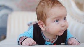 Het vrolijke babyjongen liggen stock video