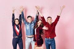 Het vrolijke bedrijf van twee meisjes en twee kerels gekleed in modieuze kleren bevinden zich en hebben pret met confettien op a royalty-vrije stock afbeelding