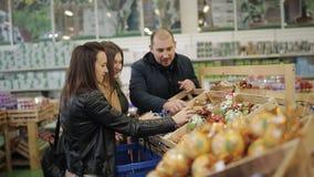 Het vrolijke bedrijf van vrienden in een supermarkt die Kerstmisspeelgoed voor de Kerstboom kiezen stock footage