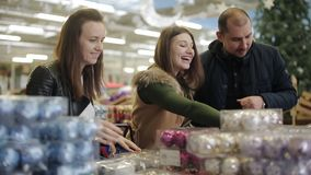 Het vrolijke bedrijf van vrienden in een supermarkt die Kerstmisspeelgoed voor de Kerstboom kiezen stock video