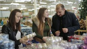 Het vrolijke bedrijf van vrienden ging winkelend voor Kerstmisdecoratie op verkoop in een supermarkt stock video