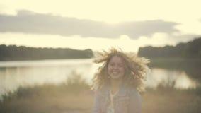 Het vrolijke blonde Europese meisje in een jeansjasje die de oever van het meer, draaien aan camera reduceren, glimlacht en geeft