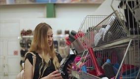 Het vrolijke blondemeisje neemt zwarte rubberlaars van mand in een winkel stock video
