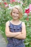 Het vrolijke blondemeisje op een gang in de tuin op een achtergrond van het bloeien bloeit Royalty-vrije Stock Fotografie