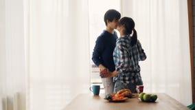 Het vrolijke de studentenmeisje en kerel dansen en kussen in keuken thuis luisterend aan muziek en ontspannende drukken uit stock videobeelden