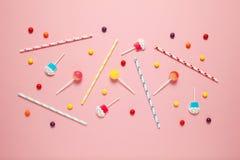 Het vrolijke decor van kinderen voor een partij, roze achtergrond Zoet suikergoed, heldere ballen, feestelijk kaarsen en stro royalty-vrije stock afbeelding